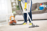 Housewife clean carpet with vacuum cleaner