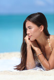 Asian beauty woman relaxing on beach during summer vacation travel. Face closeup of Chinese Caucasian mixed race fashion model posing with bracelets and sun care makeup for skincare concept.