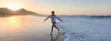 Fototapety Woman having fun runing from waves on solitary sandy beach in sunset. Waves sweeping away her traces in sand. Beach, travel, concept. Panoramic composition.