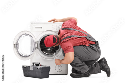 Repairman examining a washing machine Poster