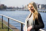 junge blonde Frau beim spazieren in Berlin entlang der Spree