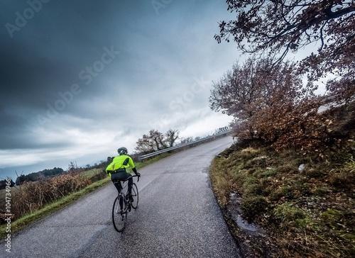 Ciclista percorre una strada dans salita sotto la pioggia Poster