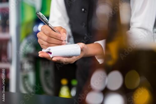 Waiter writing down an order
