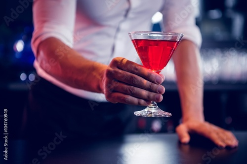 Fotografiet Bartender serving a red martini