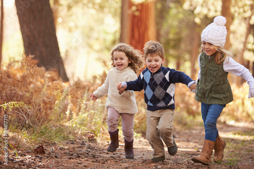 Fotografiet Group Of Young Children Running Along Path In Autumn Forest
