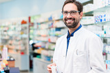 Apotheker in Apotheke steht vor Regal mit Medikamenten