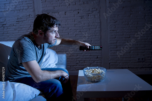 Plagát television addict man sitting on home sofa watching TV eating popcorn using remo