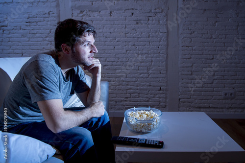 young happy television addict man sitting on home sofa watching TV and eating po Poster