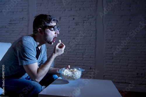 Plagát television addict man on sofa watching TV and eating popcorn in funny nerd geek