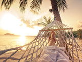 Female legs in a hammock on a background of the sea, palm trees and sunset. Vacation concept - 104883532