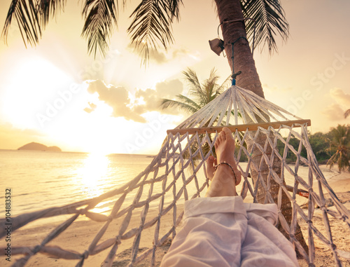 Papiers peints Mer coucher du soleil Female legs in a hammock on a background of the sea, palm trees and sunset. Vacation concept