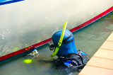 Scuba diver with snorkel and aqualung tank is cleaning a boat hull with a scrubbing pad removing all organic growth so the hull is smooth & clean resulting in higher speeds and better fuel efficiency - 104885370
