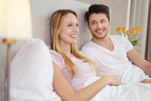 glückliches junges paar sitzt entspannt im bett