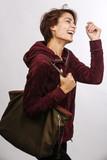 donna con giacca amaranto e borsa a tracolla ride di gusto