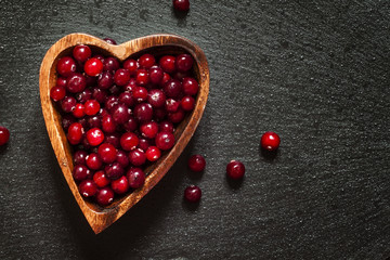 Fresh cranberries in a wooden bowl in the shape of a heart on a