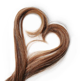 Strands of brown hair in shape of heart, isolated on white
