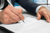 Notary signs papers at office.