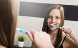 Portrait of attractive woman brushing teeth in bathroom