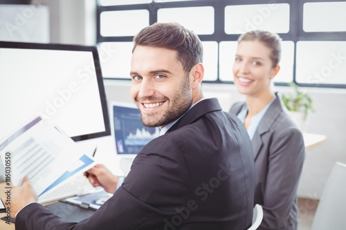 Happy business people working at computer desk