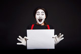 Smiling female mime holding white sheet of paper/ Crazy smiling girl mime holding white sheet of paper on black background
