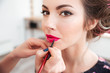 Makeup artist applying pink lipstick to lips of woman