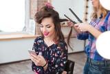 Fototapety Hairdresser applying straightener for long hair of smiling  woman