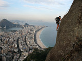Climber on rock wall with Rio de Janeiro beach on background
