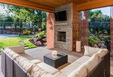 Beautiful covered patio outside new luxury home with television, fireplace, and lush green yard - 105153768