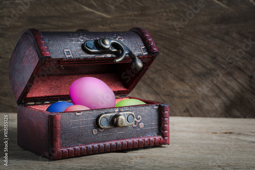Poster Treasure chest old open with easter eggs on wood background. Sti
