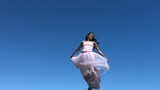 Woman wearing dress jumps in air, slow motion