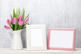 Fresh pink tulips bouquet and photo frames