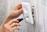 hands installing a wall power socket