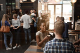 Fototapety African woman talking with friend inside busy coffee shop