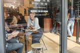 Fototapety Woman seen through glass smiling while having coffee with friend