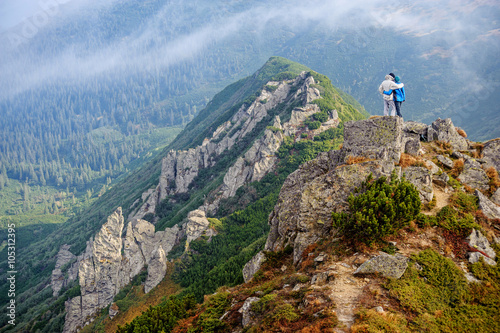 Travelers couple standing on rocky mountain summit, hugging and enjoying the view on beautiful valley Poster