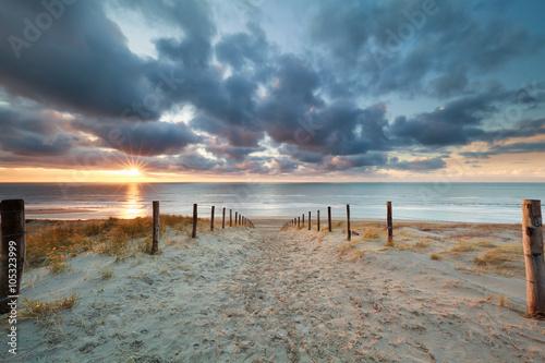 romantic path to sand beach at sunset