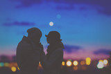 Couple in love with de-focused city lights in the background. - 105326728