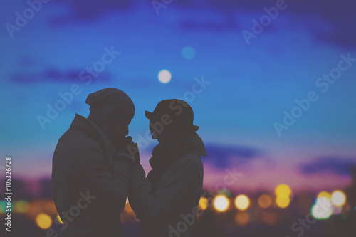 Couple in love with de-focused city lights in the background.
