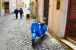 vespa parcheggiata in un vicole di Roma e coppia che è andata a fare la spesa