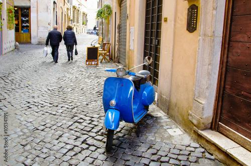 vespa parcheggiata in un vicole di Roma e coppia che è andata a fare la spesa Poster