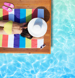 Summer holiday fashion concept - tanning woman wearing sun hat on a wooden pier view from above - 105369950