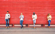 Group of multiracial fashion friends using smartphone with red wood background - Technology addiction in urban lifestyle with disinterest towards each other - Addicted people to modern mobile phones