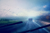 Fototapety Dangerous vehicle driving in the heavy rainy and slippery road. Raindrops on windshield of moving car on highway. Abstract blurred bad weather vehicle driving.