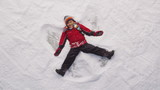 Young boy making snow angel in winter