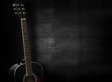 Black acoustic guitar on dark black wooden background. - 105443705