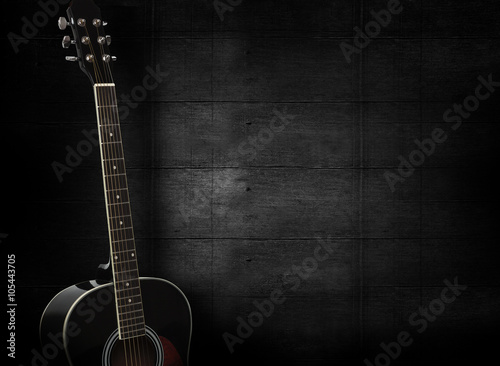 Black acoustic guitar on dark black wooden background. Poster