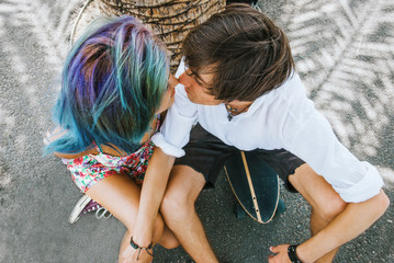 Young couple is kissing under the palm tree,sitting on the skateboard