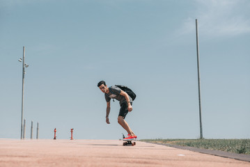 Skateboarder is flying down the wide road
