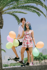 Young couple standing on the skateboard with colorful balloons