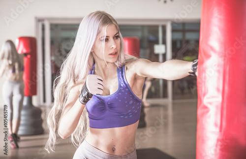 fototapeta na ścianę Woman fighter hit the heavy boxing bag